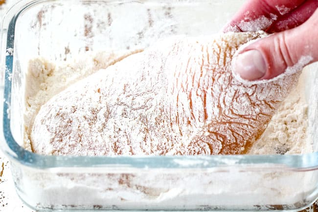 showing how to make easy chicken Parmesan by dipping chicken in flour in a glass shallow dish