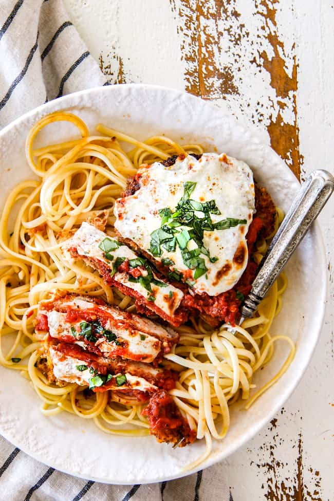 top view of easy chicken Parmesan partially sliced with spaghetti noodles in a white shallow bowl with fresh basil