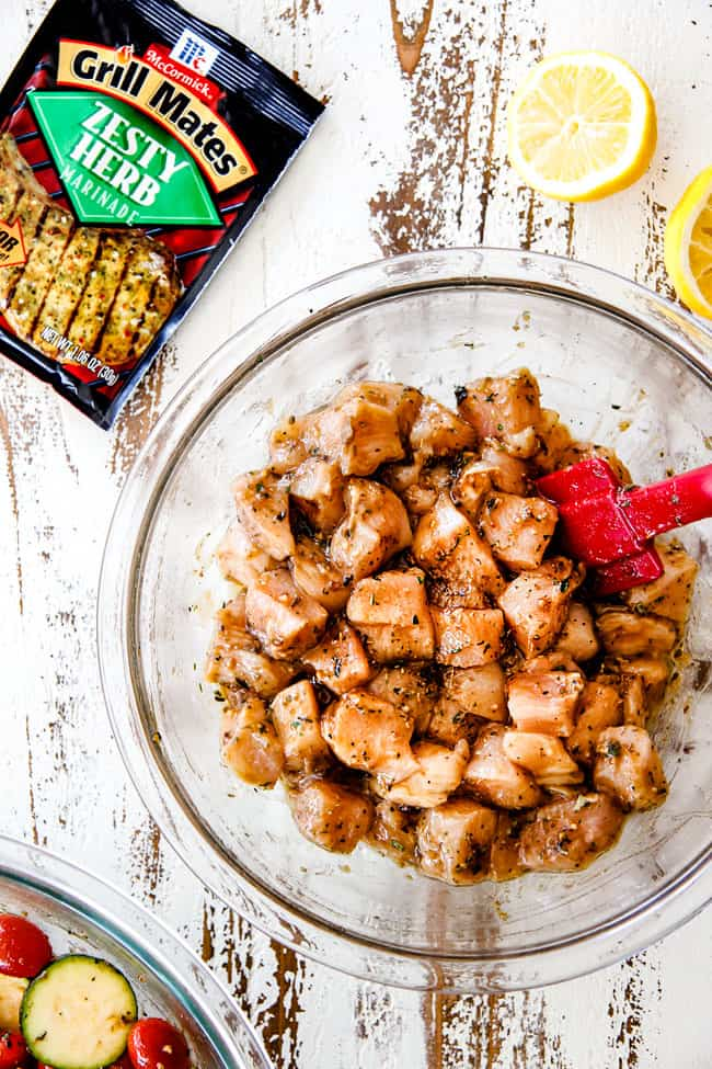 chicken in a glass bowl marinating to make chicken souvlaki
