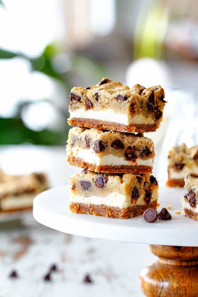 stack of cChocolate Chip Cheesecake Bars with graham cracker crust, cheesecake and cookie dough
