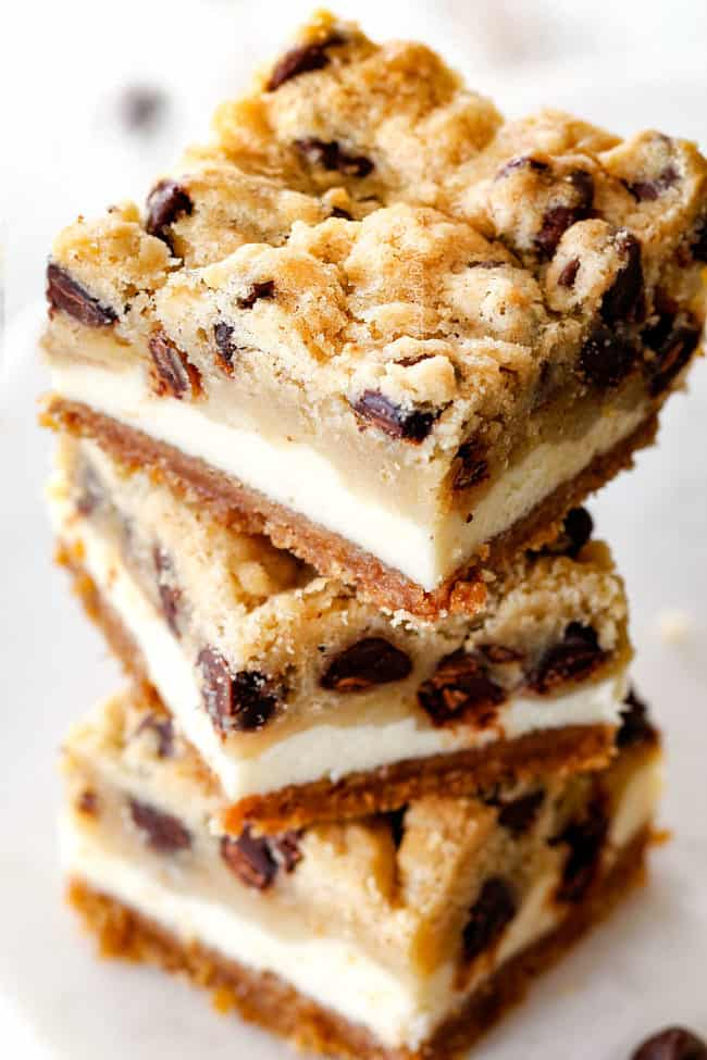 stack of cookie dough cheesecake bars with graham cracker crust, cheesecake and cookie dough