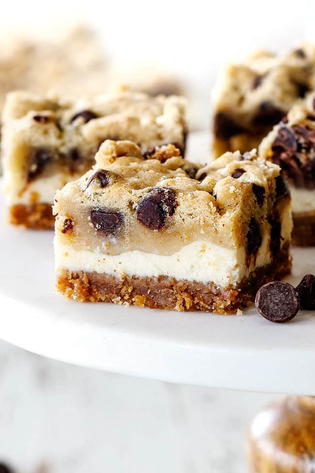 chocolate chip cookie dough cheesecake bars on a white pedestal