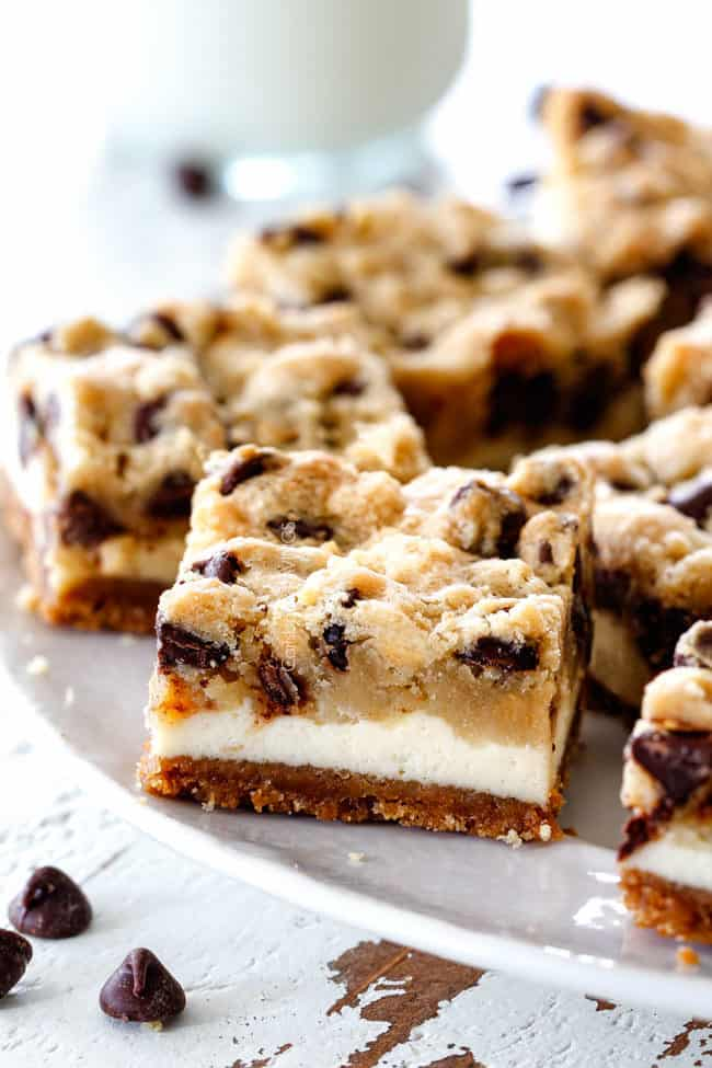 easy cookie dough cheesecake bars on a white pedestal