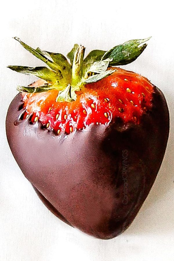 up close of chocolate covered strawberry on white parchment paper