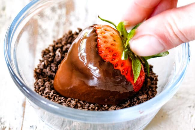 rolling chocolate covered strawberry in crushed chocolate graham cracker crumbs