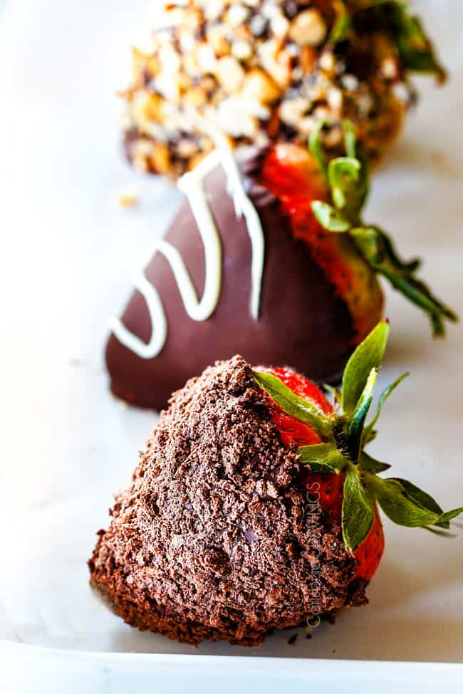 up close of Chocolate Covered Strawberry coated in crushed chocolate graham cracker on Parchment paper
