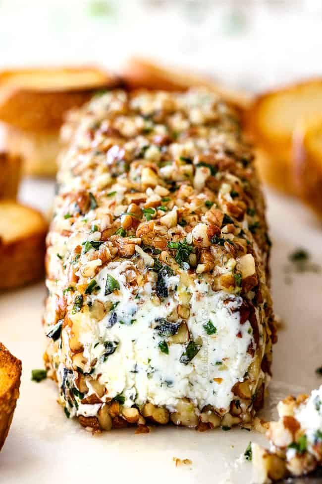 front shot of goat cheese log with garlic, zemon zest, basil, chives, parsley and rolled in pecans