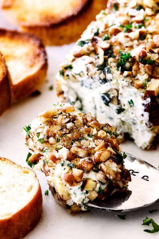 scooping part of cheese log with garlic, lemon zest, basil, chives, parsley and rolled in pecans with a knife