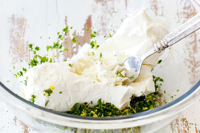 showing how to make cheese log by adding goat cheese to a glass bowl with herbs