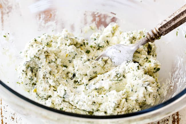 stirring together goat cheese with herbs in a glass bowls showing how to make cheese log