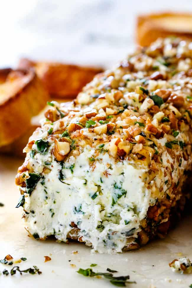 side shot of goat cheese log with garlic, lemon zest, basil, chives, parsley and rolled in pecans