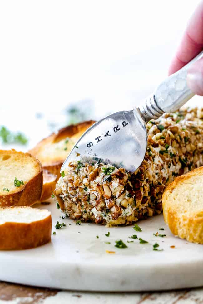 slicing cheese log with garlic, lemon zest, basil, chives, parsley and rolled in pecans with a knife