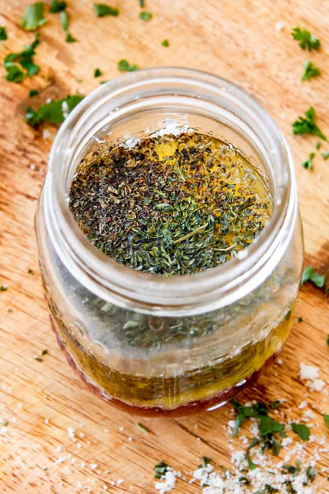 Showing how to make Homemade Italian Dressing by adding vinegar, oil, garlic, lemon juice, basil, parsley, oregano, salt and pepper to a mason jar