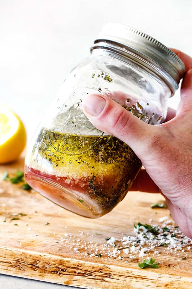 shaking Showing how to make Homemade Italian Dressing by shaking vinegar, oil, garlic, lemon juice, basil, parsley, oregano, salt and pepper in a mason jar