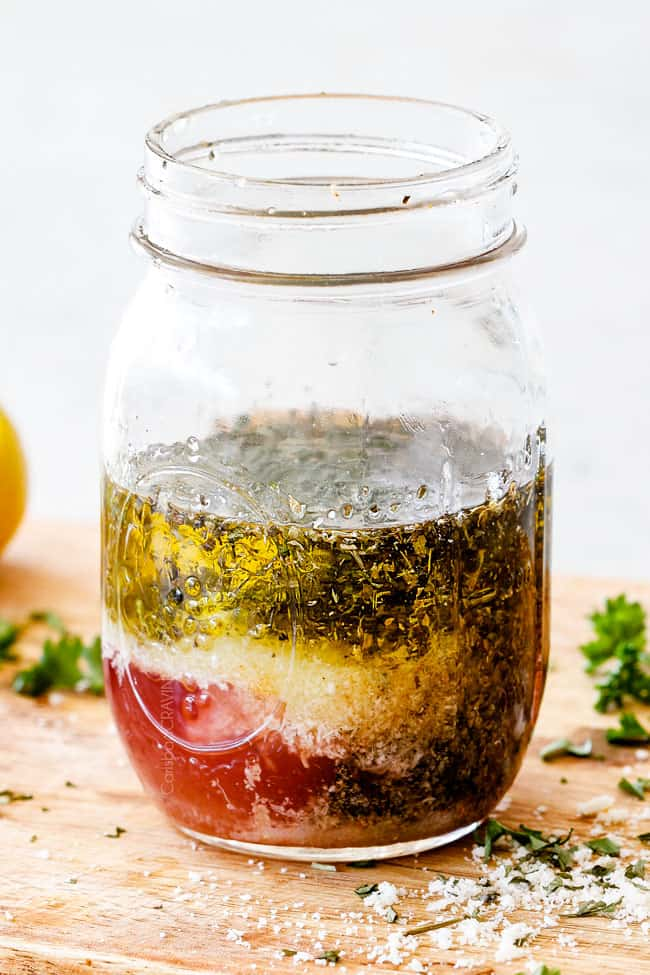 Showing how to make Homemade Italian Dressing recipe by adding vinegar, oil, garlic, lemon juice, basil, parsley, oregano, salt and pepper to a mason jar