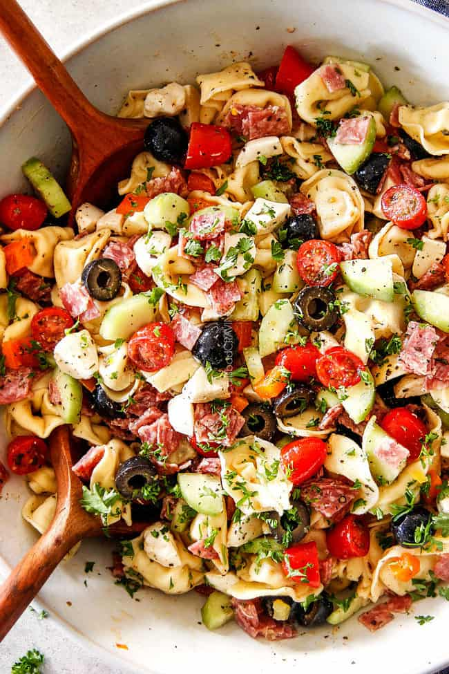 top view of easy Italian Pasta Salad with pepperoni, tomatoes, olives, cucumbers, mozzarella with wooden tongs
