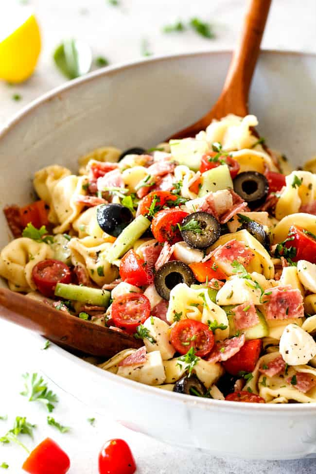 tossing together best Italian Pasta Salad with pepperoni, tomatoes, olives, cucumbers, mozzarella with wooden tongs