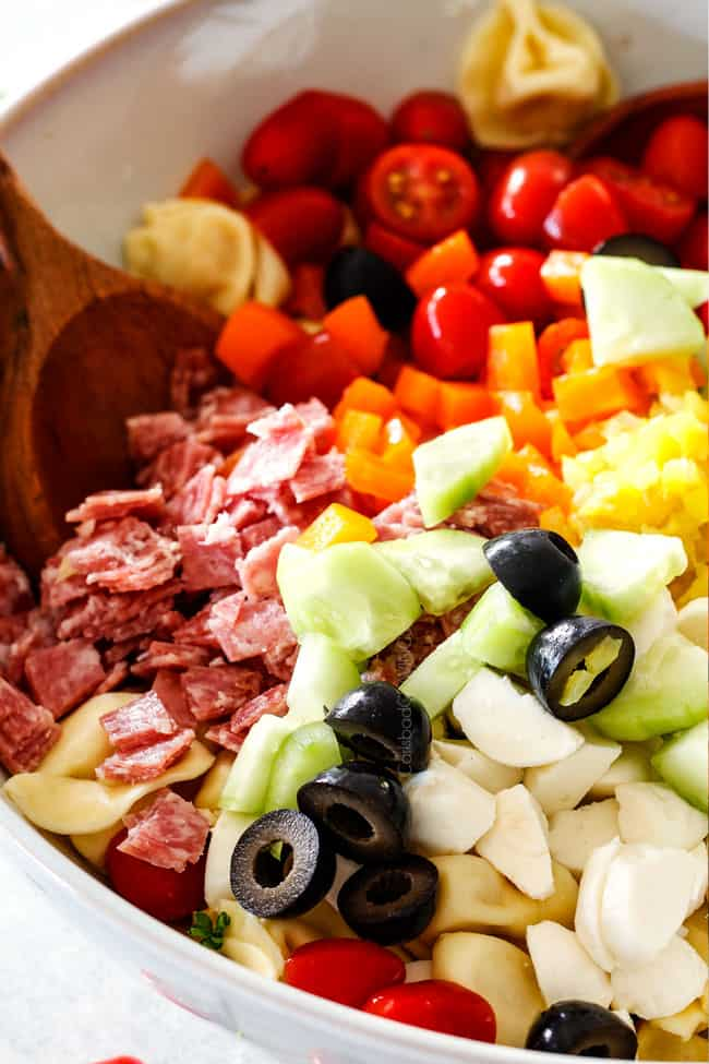 salami, tomatoes, bell peppers, mozzarella, cucumbers in a white bowl board for easy Italian Pasta Salad Recipe