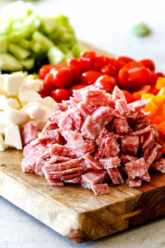 salami, tomatoees, bell peppers, mozzarella, cucumbers on a cutting board for easy Italian Pasta Salad Recipe