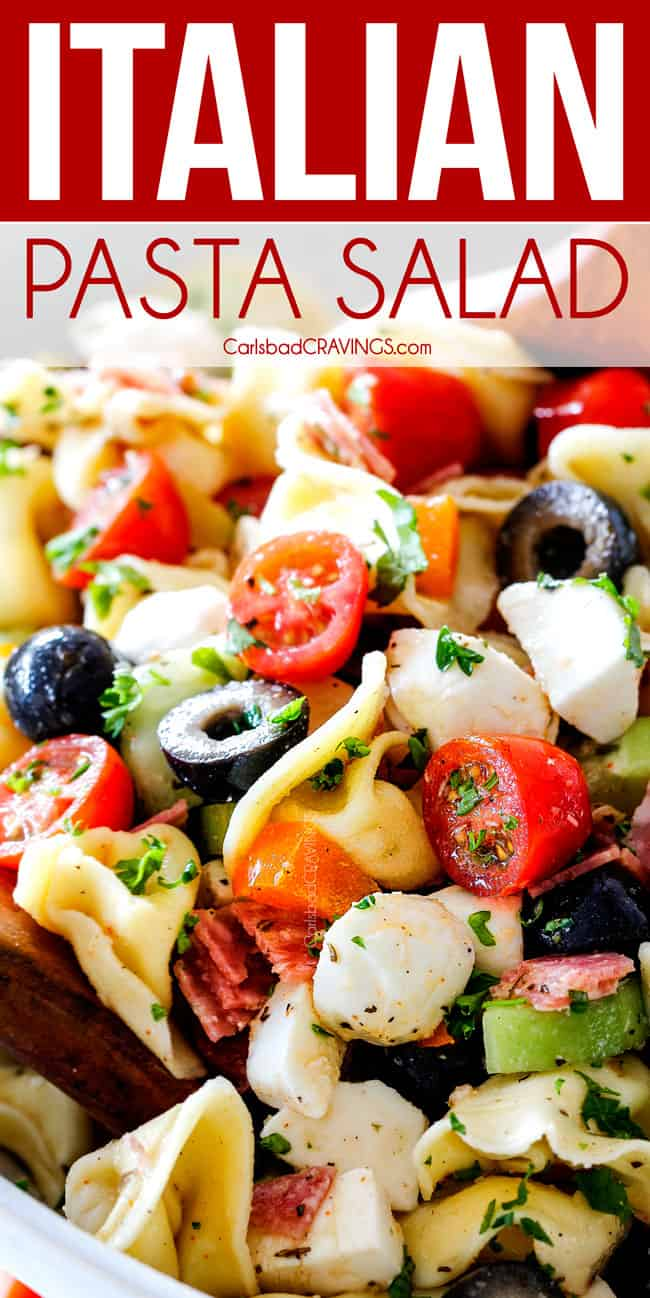 Cold Pasta Salad with Italian Dressing in a white bowl being tossed with wooden spoons