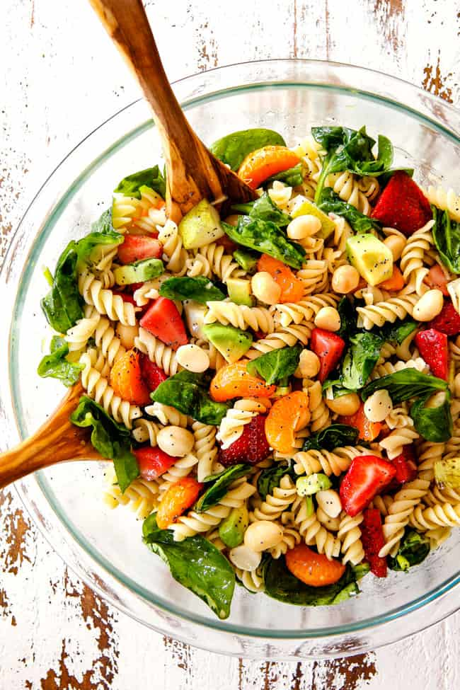 top view of pasta, strawberries, spinach, Mandarin oranges, avocados, macadamia nuts in a glass bowl with poppy seed dressing mixed together for pasta salad