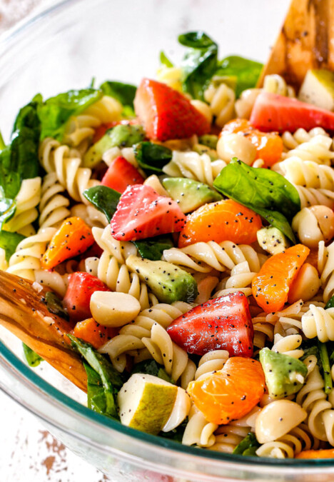 pasta, strawberries, spinach, Mandarin oranges, avocados, macadamia nuts in a glass bowl with poppy seed dressing mixed together for pasta salad