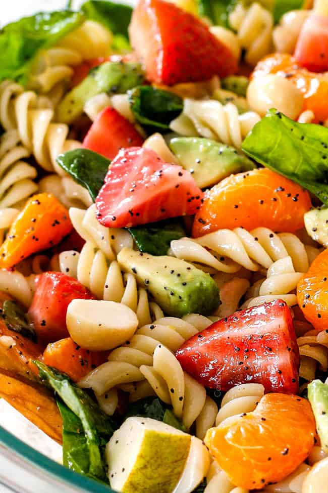 up close view of pasta, strawberries, spinach, Mandarin oranges, avocados, macadamia nuts in a glass bowl with poppy seed dressing mixed together for pasta salad