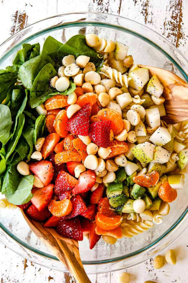 Mixing pasta, strawberries, spinach, Mandarin oranges, avocados, macadamia nuts and past in a glass bowl for pasta salad