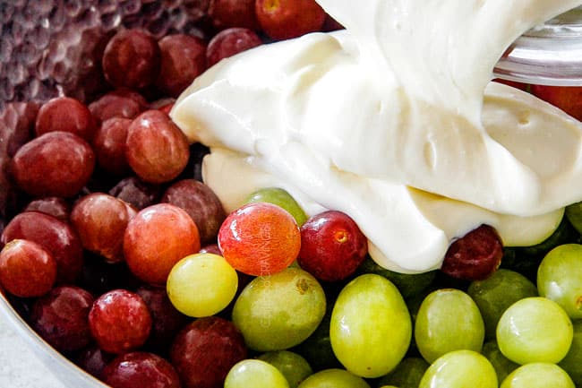 pouring cream cheese dressing over grapes showing how to make grape salad