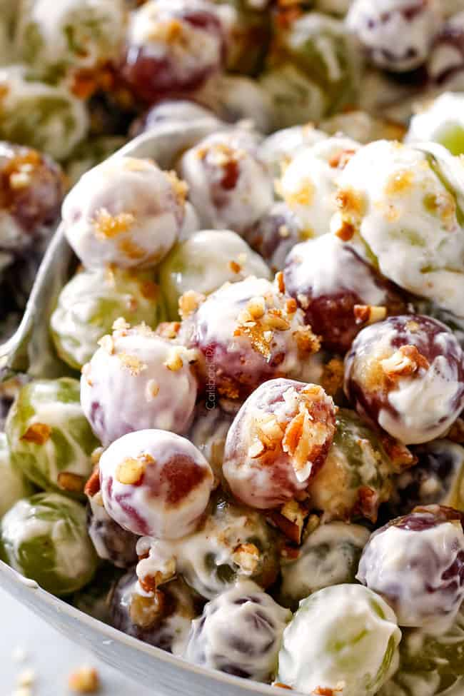 up close of best grape salad with silver tongs