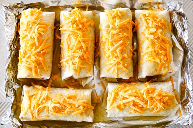 showing how to make wet burritos by adding cheese and enchilada sauce to burritos on a baking sheet