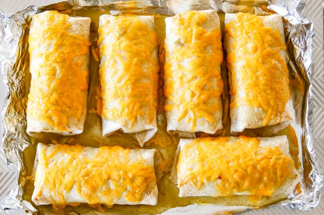 green enchilada sauce smothering wet burritos with melted cheese coming out of the oven