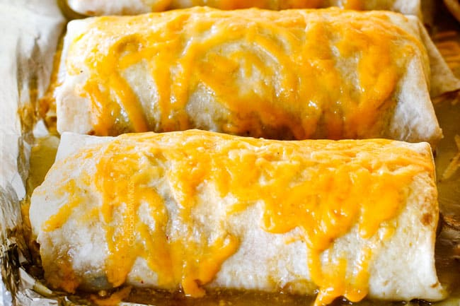 showing how to make wet burritos by melting smothering in enchilada sauce and cheese