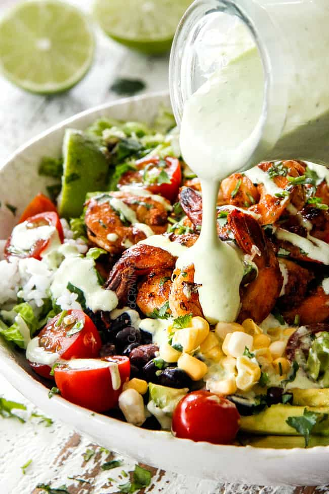 pouring creamy Cilantro Lime Dressing over a bowl of shrimp, corn, tomatoes and black beans