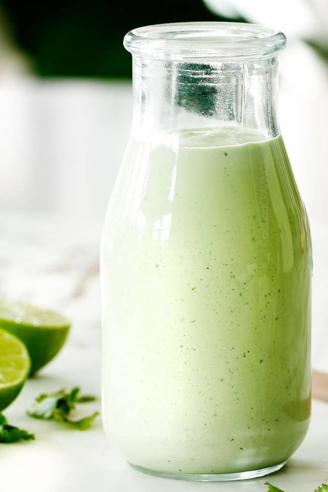 Cilantro Lime Dressing in a glass jar on a white cutting board