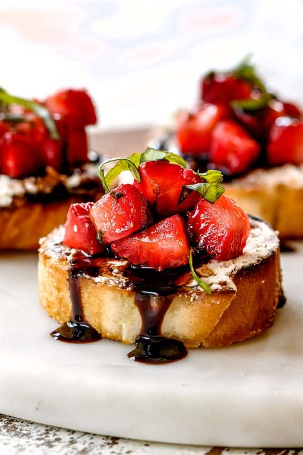 side view of best Strawberry Goat Cheese Bruschetta on a white cutting board with Balsamic Reduction