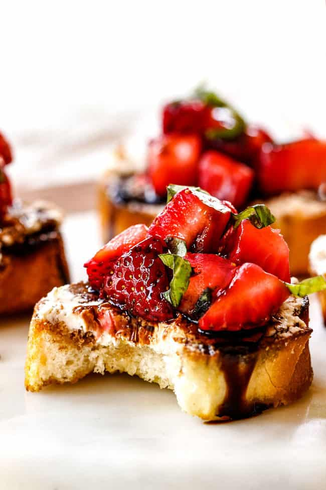 side view of strawberry goat cheese bruschetta on a white cutting board with a bite taken out