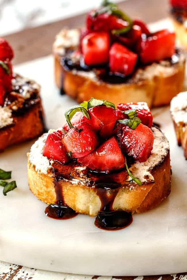 Strawberry Goat Cheese Bruschetta on a white cutting board with Balsamic Reduction
