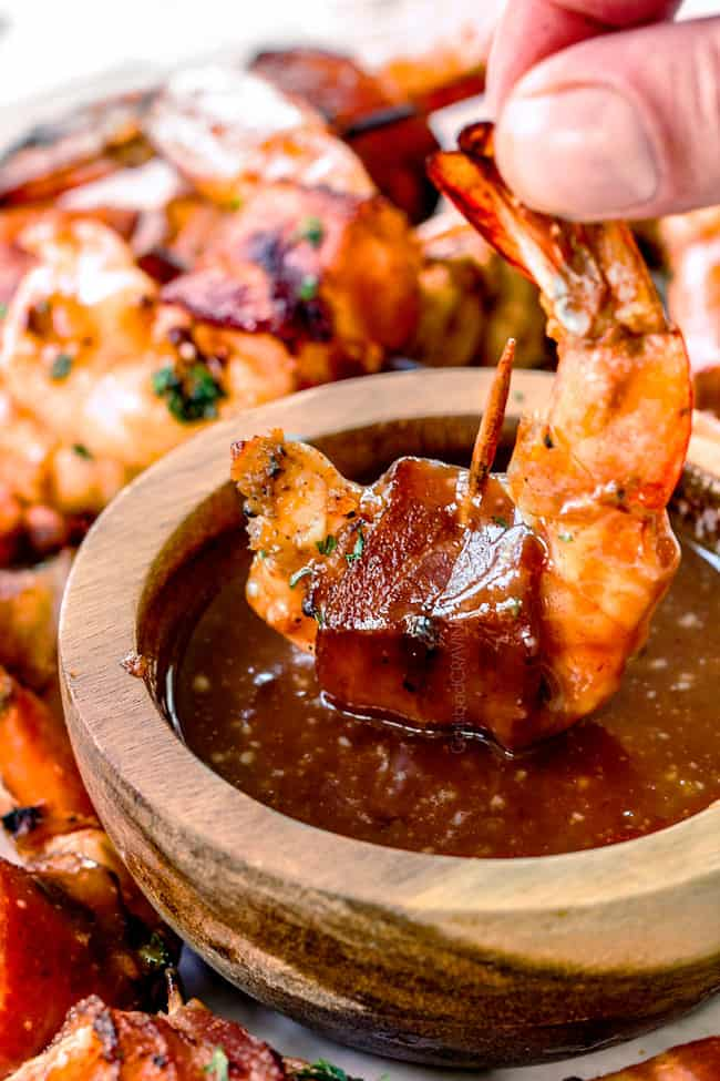 dipping grilled bacon wrapped shrimp in homemade cocktail sauce