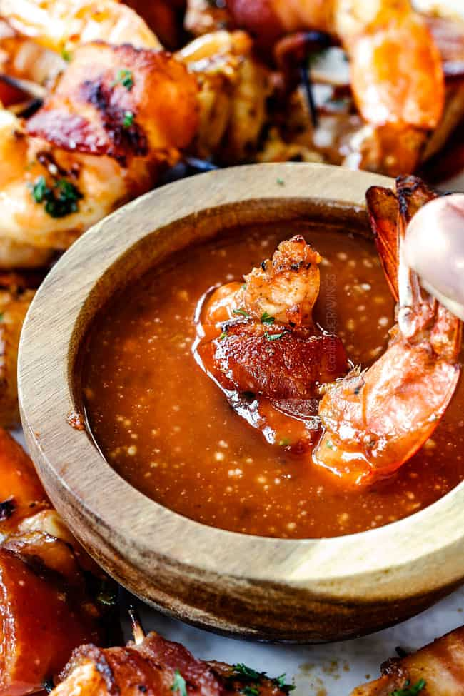 dipping bacon wrapped shrimp in cocktail sauce