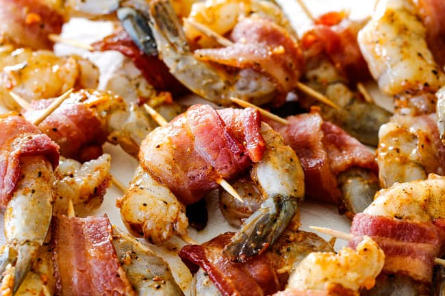 showing how to make bacon wrapped shrimp by wrapping bacon around raw shrimp and securing with toothpick