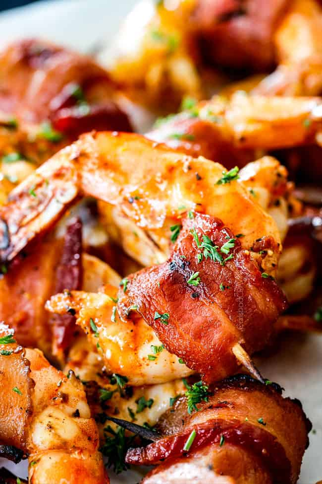 up close of bacon wrapped shrimp on a white plate