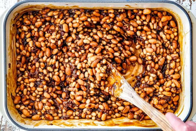 Showing How to make Boston Baked Beans by stirring navy and pinto beans together with homemade sauce