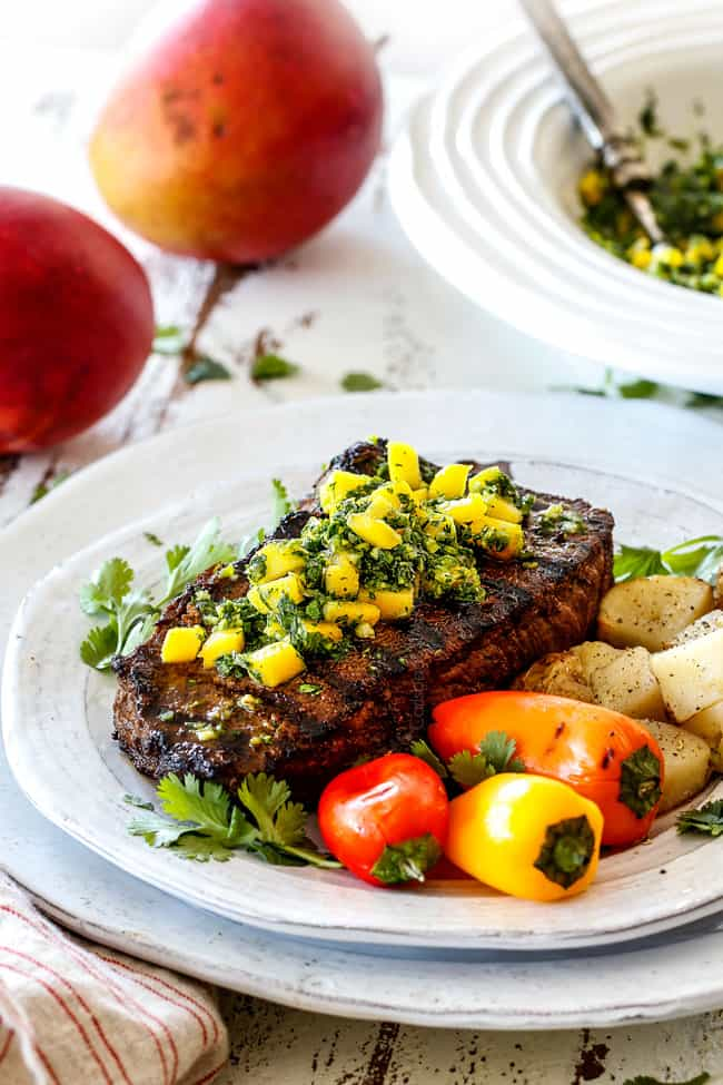 Chimichurri steak on a white plate with chimichurri
