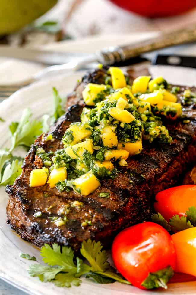 up close of juicy Brazilian Chimichurri steak on a white plate