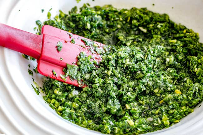 showing how to make chimichurri for Chimichurri steak by adding olive oil, red wine vinegar to cilantro and parsley in a white bowl