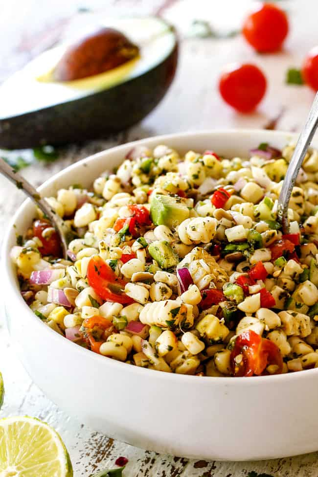 Tossing Fresh Corn Salad with avocado, red bell peppers, jalapeno, cilantro, sesame seeds mixed together in a white bowl