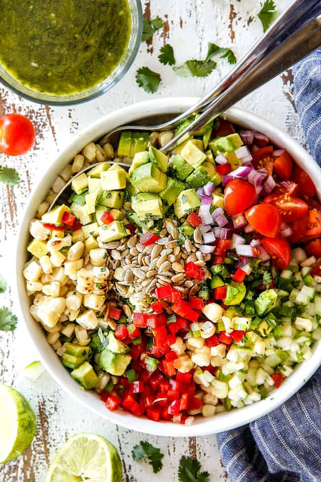 top view of corn salad ingredients in a white bowl with canned corn, avocados, tomatoes, jalapenos, cilantro, red onions, jalapeno, sesame seeds