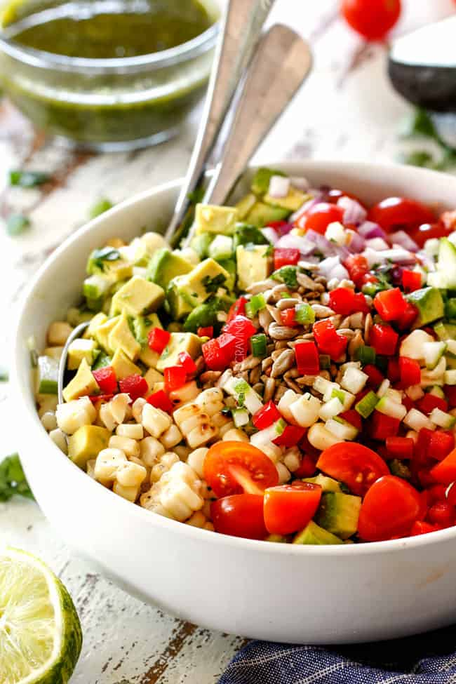 side view of corn salad ingredients in a white bowl with canned corn, avocados, tomatoes, jalapenos, cilantro, red onions, jalapeno, sesame seeds
