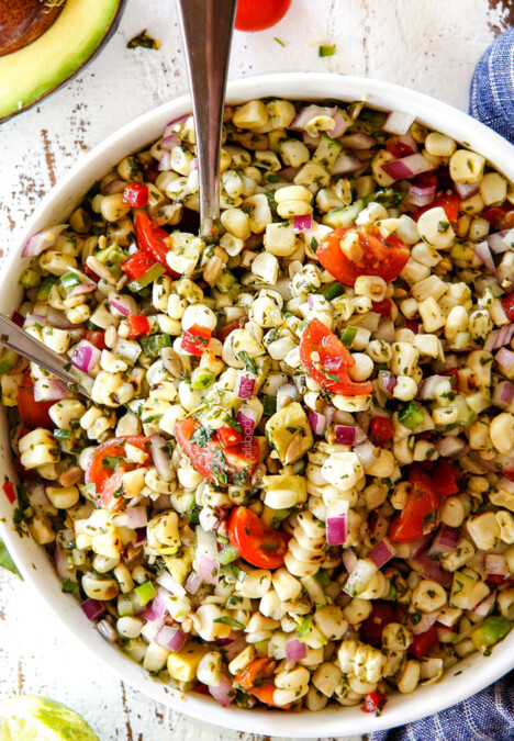 Fresh Corn Salad mixed together in a white bowl with silver spoons
